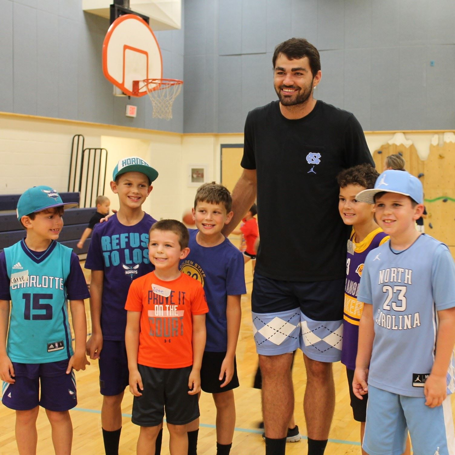 Boys posing with Luke Maye at basketball court